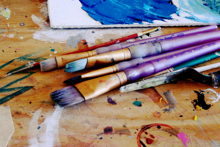 Paintbrushes on a messy table.