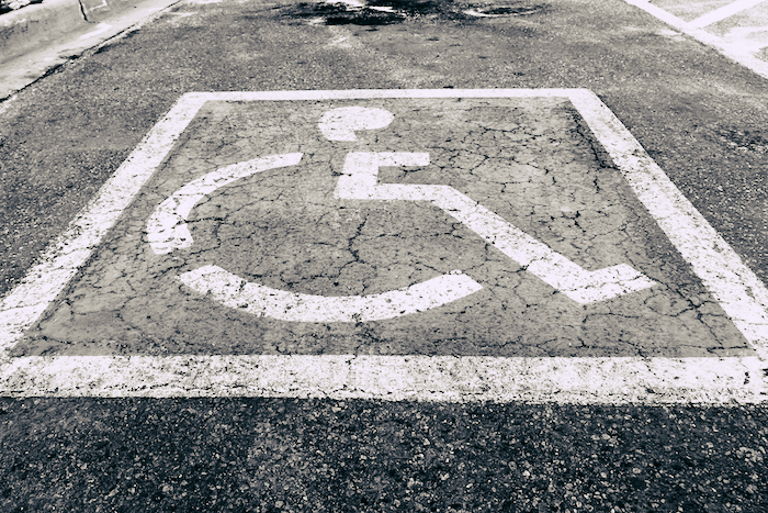 Black and white universal symbol of access painted on concrete.
