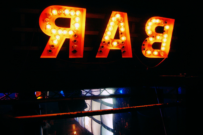 "Sign reading ""BAR"" in stage lights."