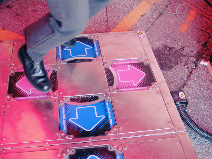 DDR dance pad with shoes dancing over it.