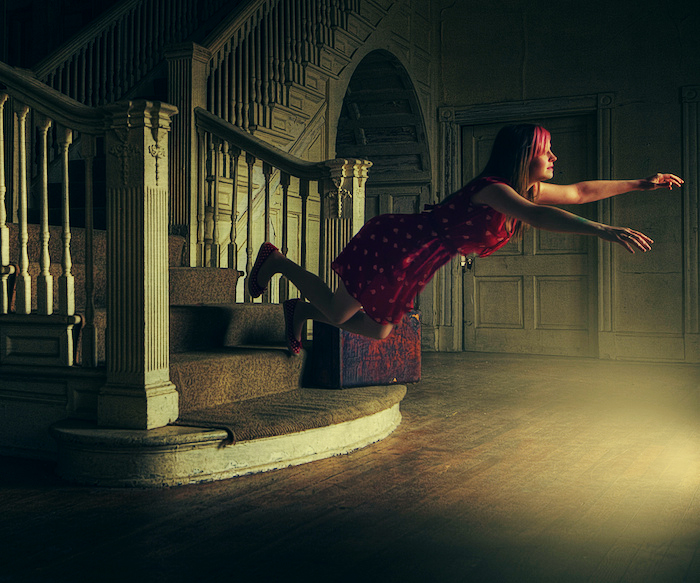 Woman at the bottom of stairs, appearing to be swimming through the air as if suspended in water or levitating.