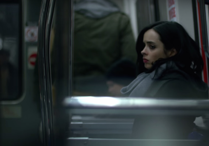 Jessica Jones alone and anxious on a subway train.