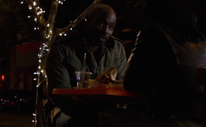 Luke Cage seated at an outdoor table with Jessica (off camera).