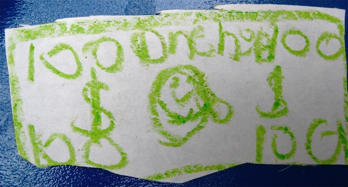 Play money, drawn in crayon on paper.