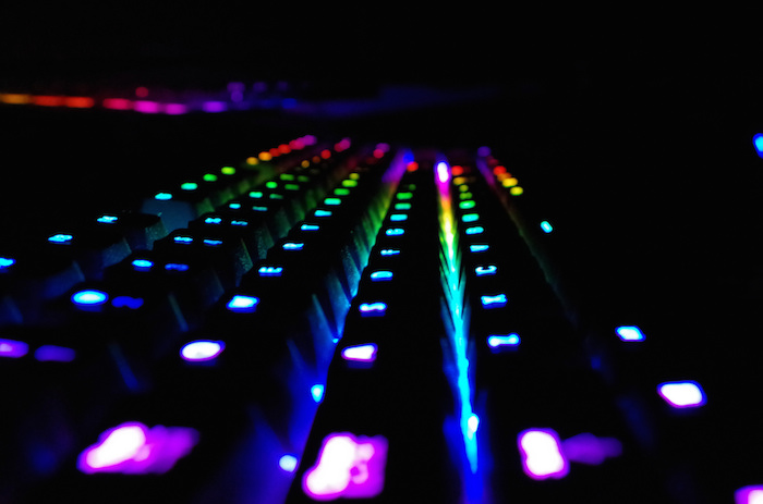 A keyboard with the keys lit up in rainbow colors.