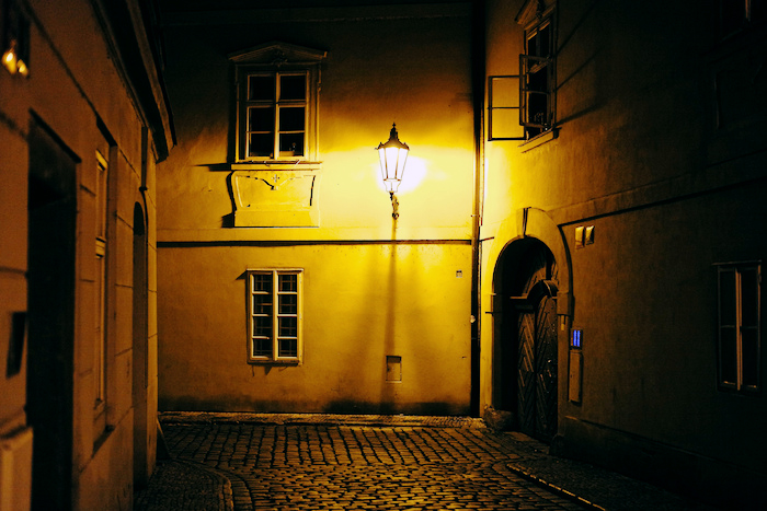 Gaslight illuminating an alley.