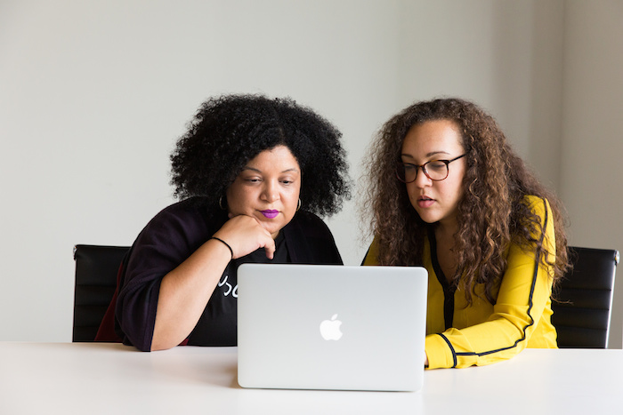 Two women collaborating on a computer.