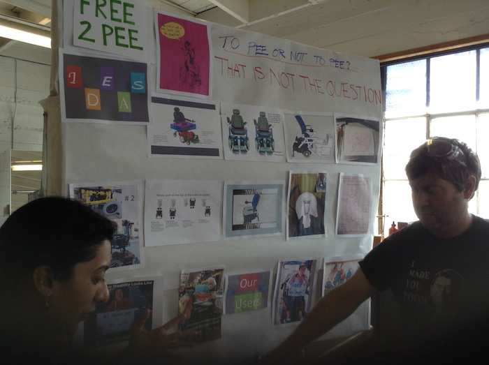 Image of a large board that contains various pieces of paper with images and lists from Team Free To Pee that's used for the presentation during the judging portion of the makeathon. Two individuals are in front of the board looking downward at an object.