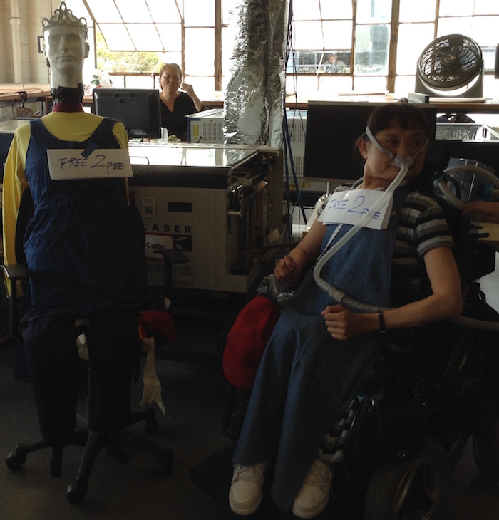 Photo of the workshop space. On the left is a mannequin used for the Team Free To Pee prototype. The mannequin is dressed in blue overalls and a yellow shirt. On the right of the image is an Asian American woman wheelchair user who is wearing a mask around her face.