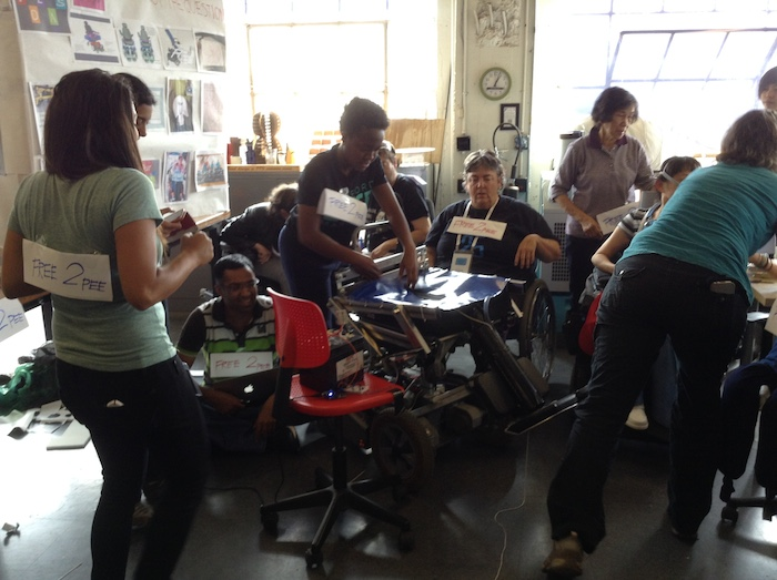 Photo of the workshop space. Various members of Team Free To Pee are involved in various activities—some are bent over working on a blue plastic prototype seat, some are standing, some are sitting and some are in wheelchairs in the middle of the action.
