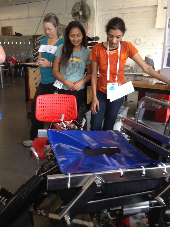 Photo of the workshop space. Two members of Team Free To Pee, young South Asian women, are standing in front of the prototype that consists of a seat made of blue plastic with a hole in the middle.