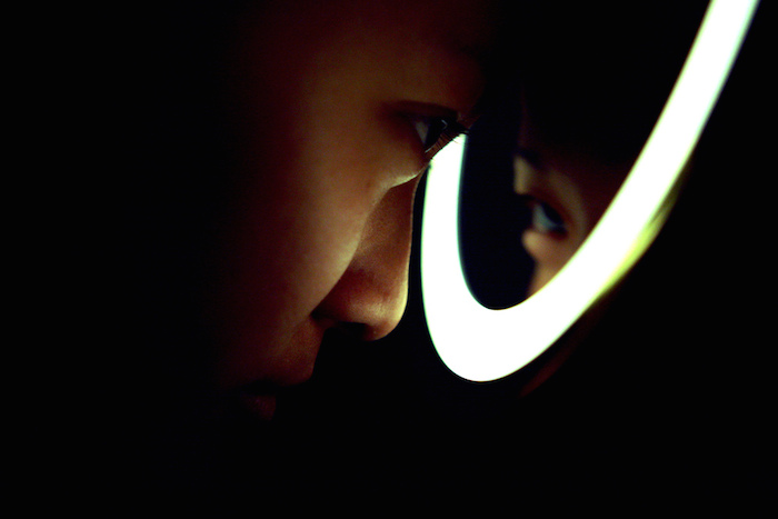 A person pressing their face into a light-rimmed mirror.