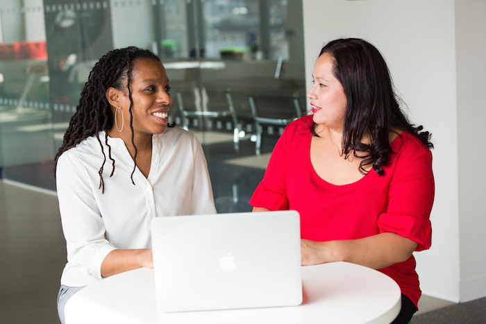 Two women of color in technology talking over a computer.