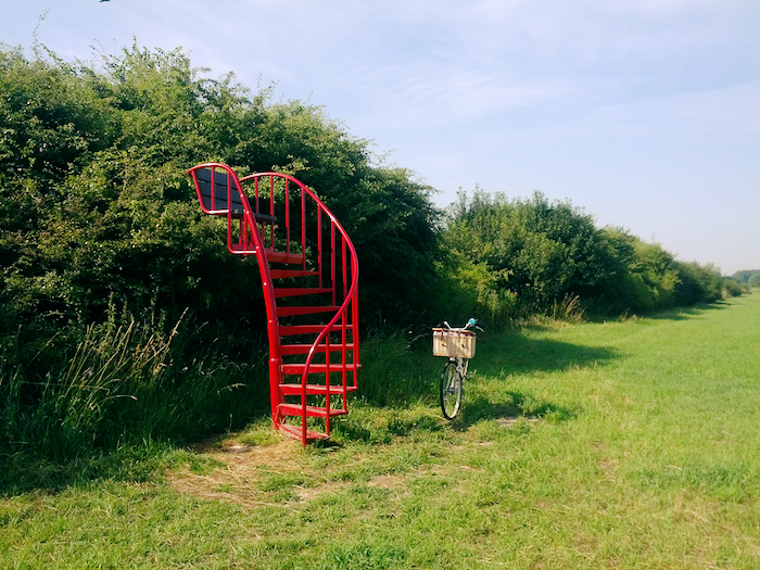 A winding ladder, out of place in the middle of a green field, a bike alongside it.