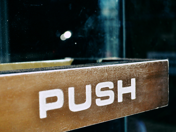 "A door with a handle reading ""Push."""