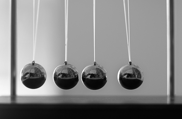 Series of metal balls suspended on string.