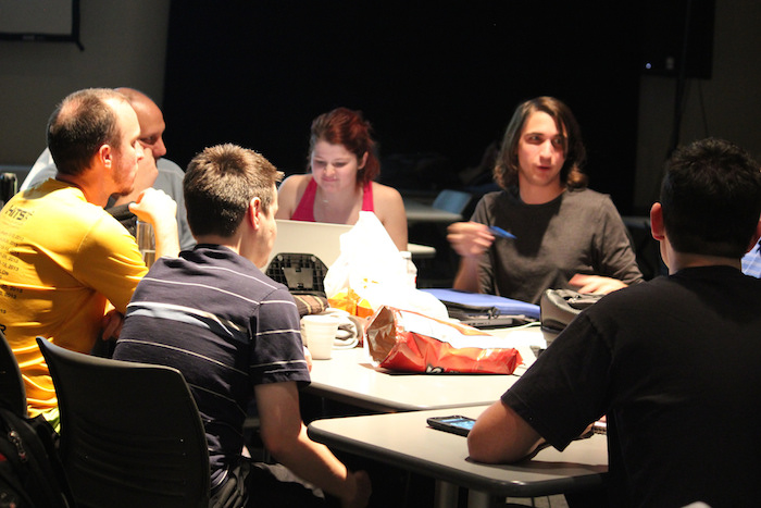 Participants in a GGJ event, crowded around a table.