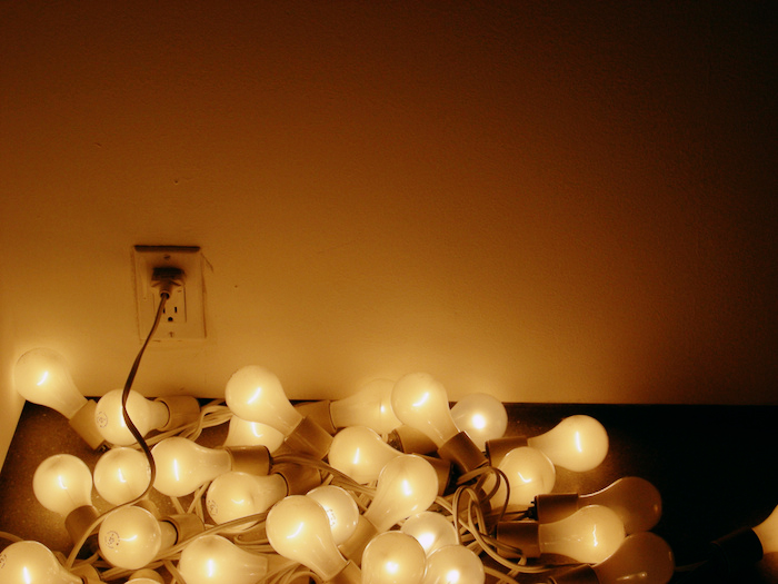 A pile of light bulbs, connected to a power outlet, strewn on the floor.
