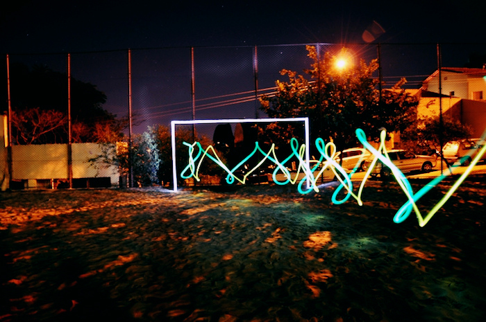 Arches of neon lights stretching across an outdoor field, like an animate graph.