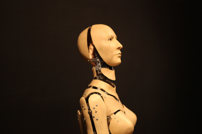"A humanoid robot gazes into space, mechanical parts visible between plates of ""flesh""."