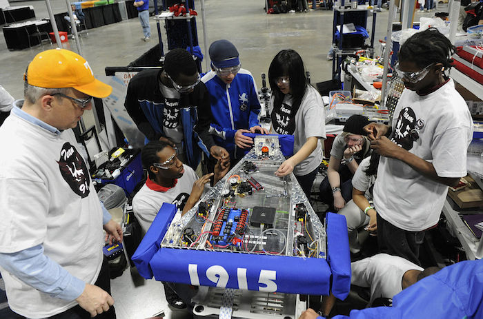 Students gathered around a collection of electronics, building a robot for a competition.