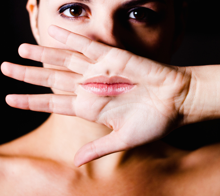 A woman holding her hand, palm out to the viewer, over her mouth. Her lips are superimposed onto her open palm.