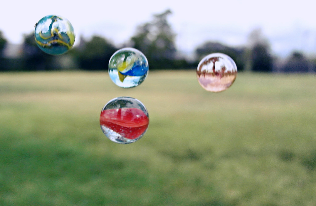 Photo of brightly-colored marbles, suspended in air over a field.