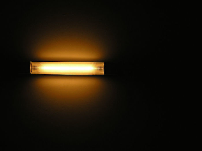 A ceiling light glowing in a dark room.