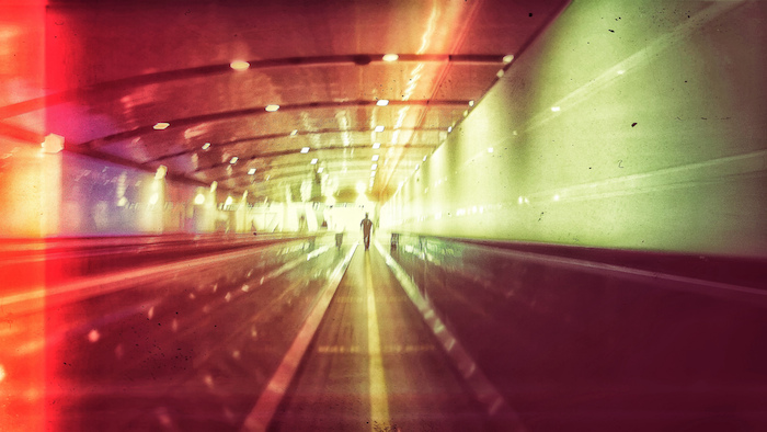 Picture of a tunnel with streams of car lights on the walls and ceilings, with a man standing far away from the camera.