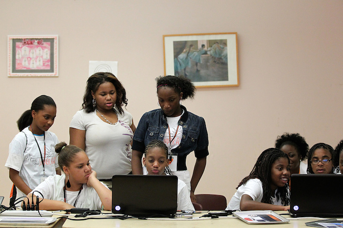 Teens of color working in groups on a few laptop computers.