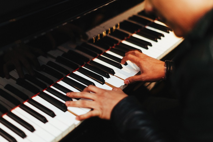 Close-up of a person's hands playing piano.