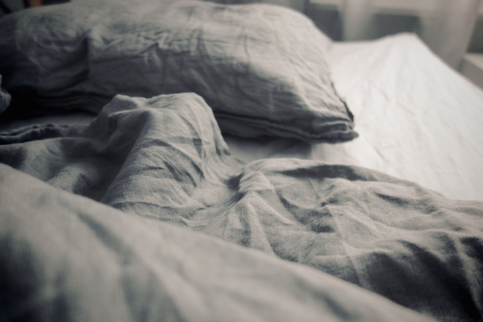 Tangled sheets in a bed.