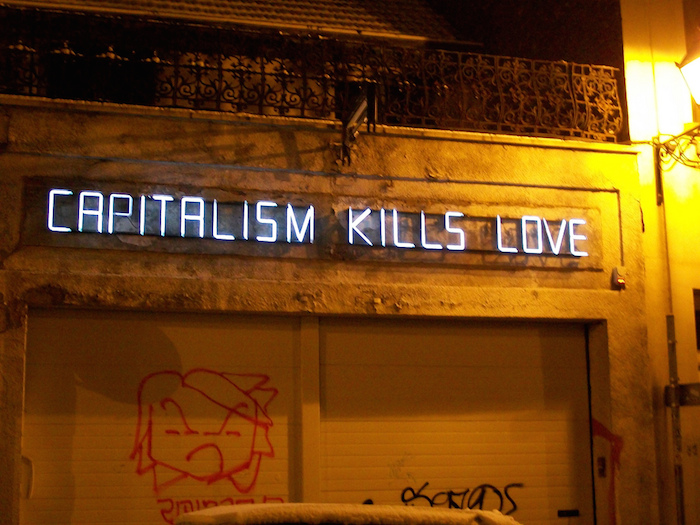 An electric sign above a garage reading 'Capitalism Kills Love.'