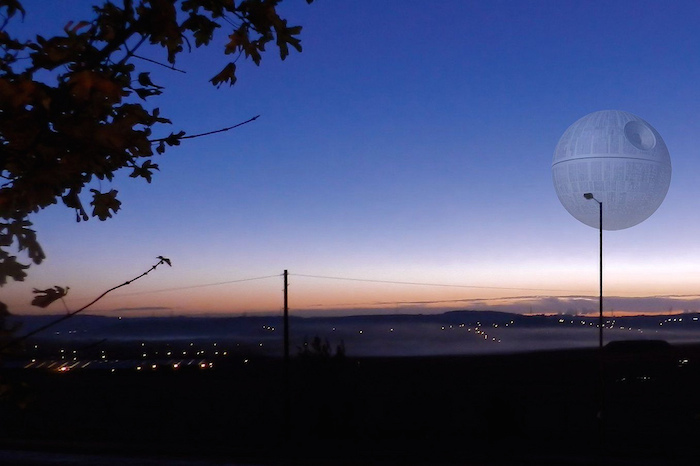 The Death Star rising above an urban landscape with power lines in the distance.