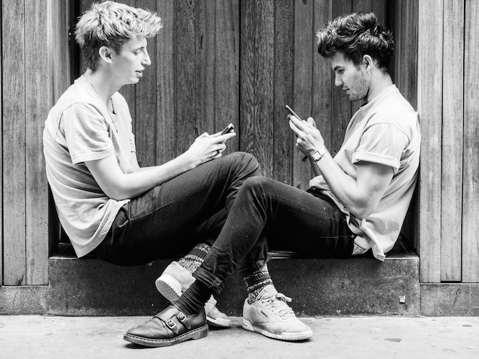 Two young white men sitting next to each other in a doorway, both typing on their mobile phones.
