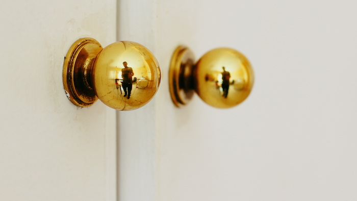 Door knobs with a figure reflected in them.
