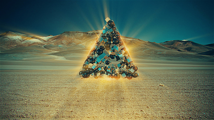 Computer generated, glowing pyramid made out of shiny baubles against a background of sand dunes.