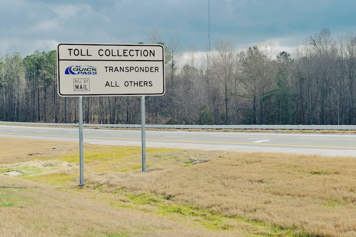 "Sign that reads ""Toll Collection"" on a highway."