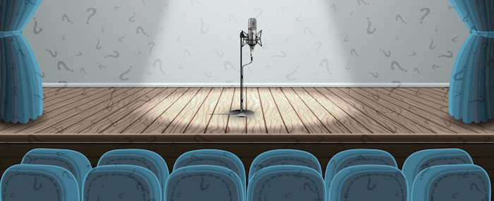 Microphone standing alone on an empty stage.