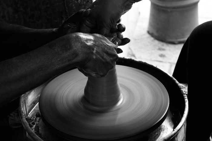 Two people working together to make something on a pottery wheel.