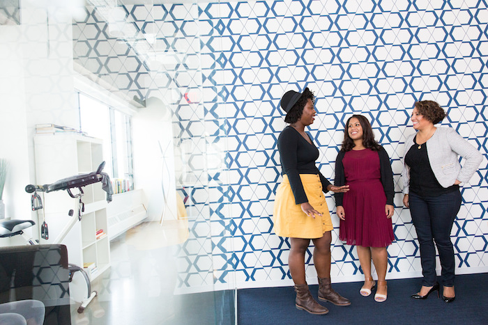 Women of color in tech standing together and laughing, collaborating.