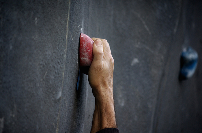 A hand gripping a hold on a climbing wall.