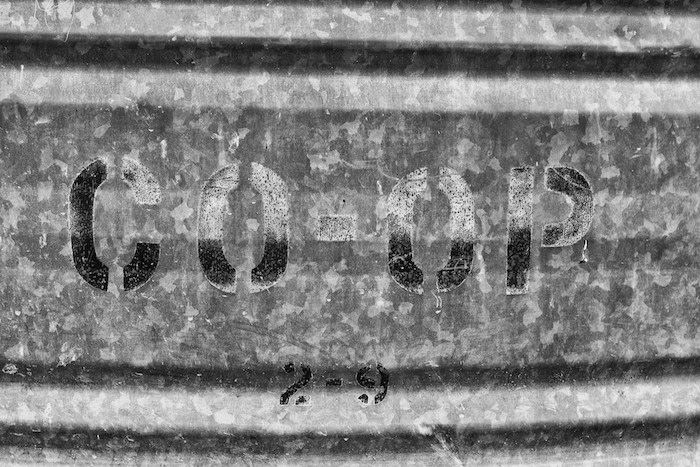 "The words ""coop"" stamped in metal."
