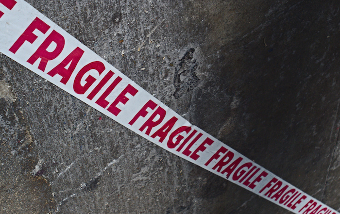 Tape that reads 'fragile' stretched against cement.