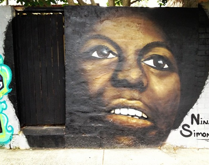 Beautiful street art portrait of Nina Simone, eyes upward and lips parted, on a large wall.