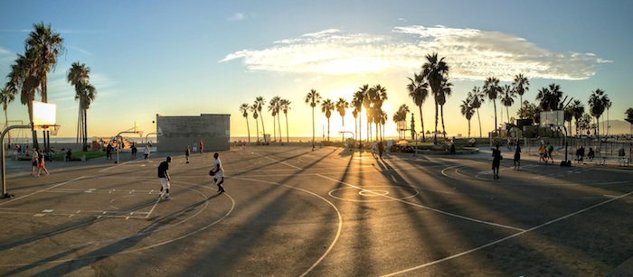 Wide, sweeping shot of people playing basketball on an outdoor court at sunset.