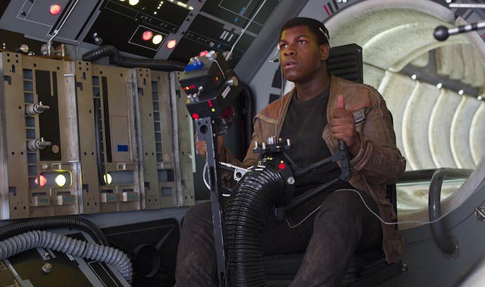 Actor John Boyega as Finn in The Force Awakens, sitting at the weapons station of a spacecraft.