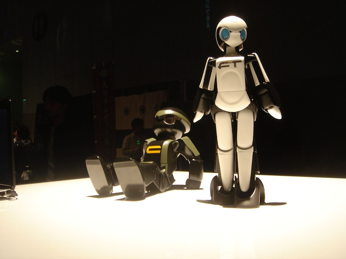 Two astronaut-like robots illuminated on a stage for display, one standing and one sitting.