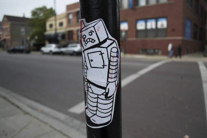 A sad-looking humanoid robot sticker plastered on a sign pole outdoors.