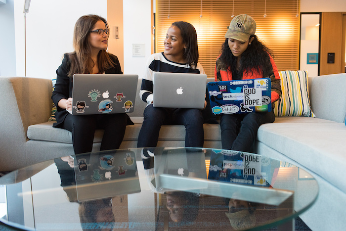 Three women of color sitting on couches in an office environment, talking and working on their laptops.